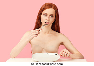 Depressed, gloomy exhausted woman eating one green pea with fork and knife.