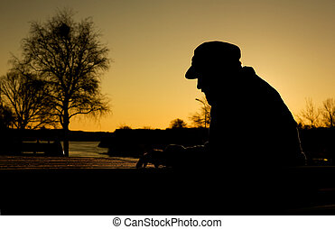 Depressed Man - A depressed thoughtful man by the water at...