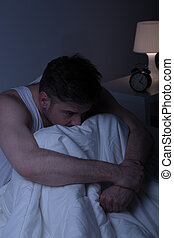 Depressed man alone in bed