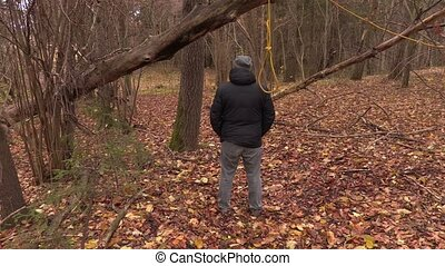 Depressed man behind gallows noose