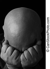 A depressed man pressing his face into his folded hands