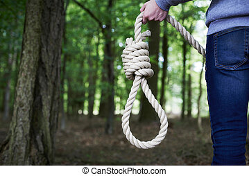 Depressed Man Contemplating Suicide By Hanging In Forest