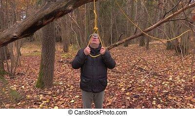 Depressed man crying near gallows noose
