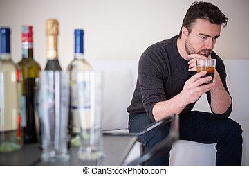 Depressed man drinking hard liquor at home