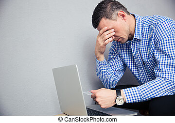 Depressed man holding credit card  over gray background