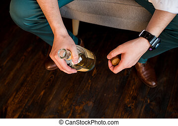 Depressed man holding in his hands a bottle of whisky sitting in armchair