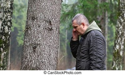 Depressed man leaning on a tree