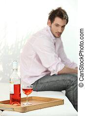 depressed man looking a wine bottle