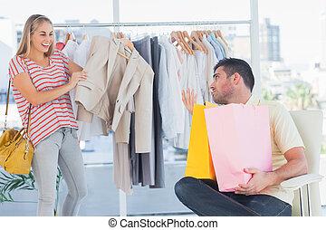 Depressed man looking at his shopaholic girlfriend