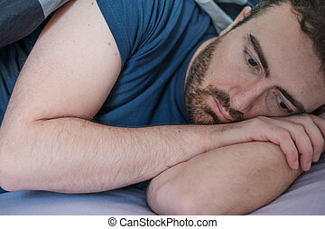Depressed man lying in his bed feeling bad