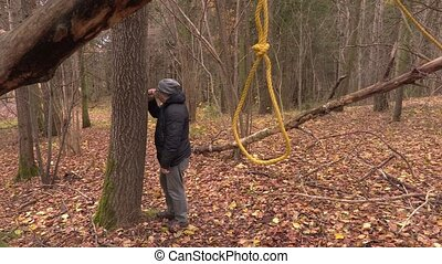 Depressed man near tree with gallows noose