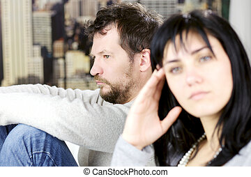 Depressed man not looking at wife after fight