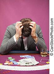 Depressed man playing poker - Depressed man sitting at table...