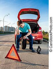 man sitting on spare wheel near broken car