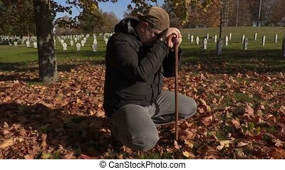 Depressed man with crutch in cemetery in autumn