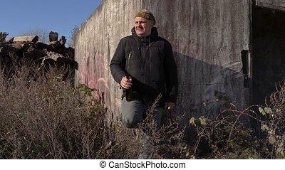 Depressed man with wine bottle near abandoned building