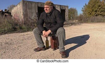 Depressed man with wine bottle sitting on suitcase