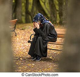 depressed muslim female sitting on the bench