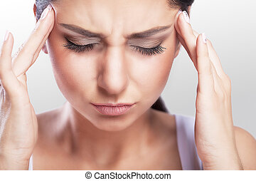 Depressed overweight is a beautiful young woman with black hair who suffers from severe headaches and a touching head. Migraine. Treatment. The concept of health.