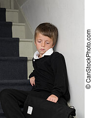 Depressed Primary School child sitting on the stairs.