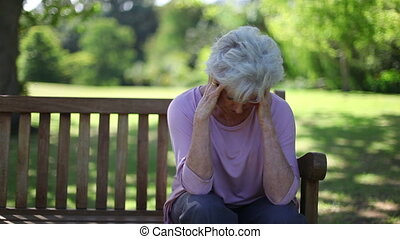 Depressed retired woman sitting on a bench