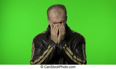 Miserable depressed dramatic rocker man in brown leather jacket crying and wiping away tears, experiencing loss defeat, feeling lonely and desperate in his grief. Portrait of guy biker on chroma key
