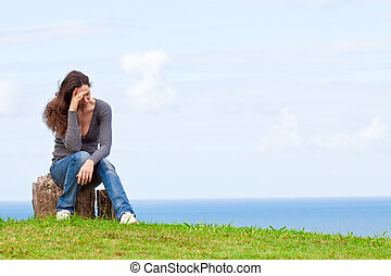 Photo of a depressed and upset young woman sitting outside with her head in her hands
