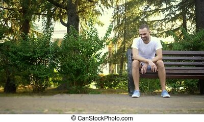 Depressed Sad young man sitting alone on a bench in a summer park. copy space