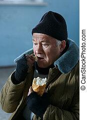Depressed senior-aged beggar eating bread. - Poor food....