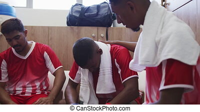 Front view of a three mixed race male football players wearing a team strip, sitting in changing room, resting with towels over their shoulders, in slow motion