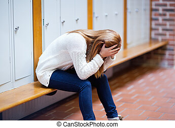 Depressed student sitting on a bench in a corridor