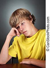 Depressed Teen - a teenaged boy sits looking depressed, his...