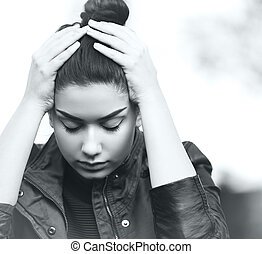 Depressed teen girl showing sadness and stress outdoor