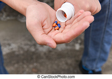 Depressed teenage boy with many tablets in hand, wants to take an overdose. concept of loneliness, misunderstanding, lack of integration