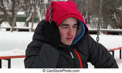 Depressed teenager on swing in wint