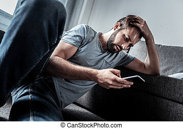 Depressed unhappy man reading a message