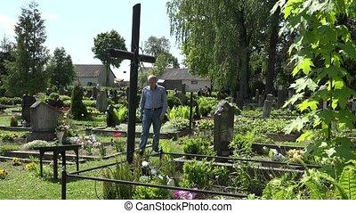 Depressed widower man sit on bench near wife tomb in sorrow. 4K