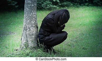 Depressed woman in focus near tree
