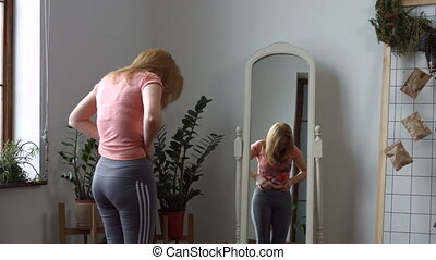 Depressed middle aged plus size woman looking at herself reflection in the mirror and pinching her stomach fat. Beautiful redhead woman dissatisfied with her appearance in mirror in domestic interior