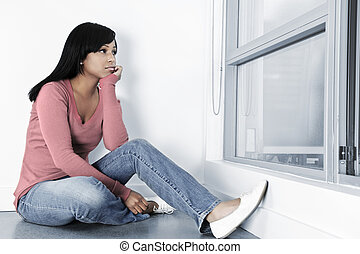 Depressed black woman sitting against wall on floor looking out window