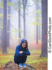 Depressed woman standing alone in forest