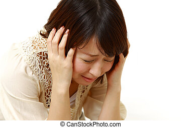 depressed woman - studio shot of young Japanese woman on...