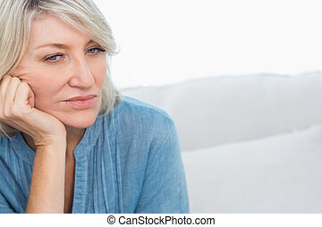 Depressed woman thinking at home on couch