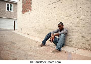 Depressed Young African American Man Leaning Against Alley Wall