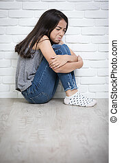 Depressed young asian girl sitting on floor at home