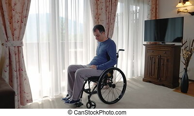 Depressed young man in wheelchair near the window at home or...