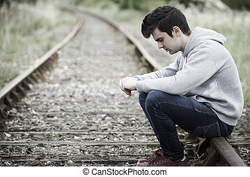 Depressed Young Man Sitting On Railway Track