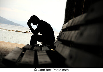 depressed young man sitting on the bench - Young man sitting...