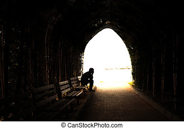 depressed young man sitting on the bench - young sad sitting...