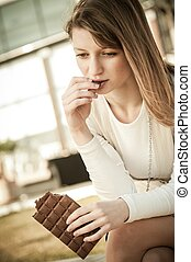 Depressed young woman eating chocolate